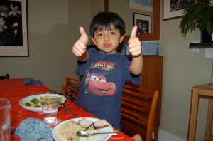 child two thumbs up at dinner
